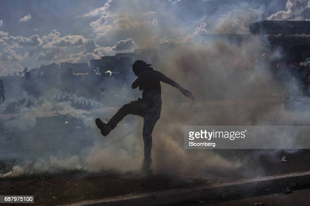 A demonstrator kicks a tear gas cannister back at riot police during protests outside of the National Congress demanding the resignation of President...
