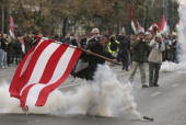 A demonstrator kicks away a tear gas cannister fired by police during violent street protests October 23 2006 in Budapest Hungary The country is...