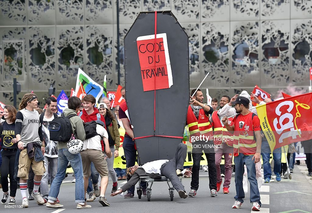 A demonstrator lies in front of a coffin symbolizing the labour code during a protest against controversial labour reforms, on June 28, 2016 in Nantes, western France. People took to the streets in France on June 28 in the latest protest march in a marathon campaign against the French Socialist government's job market reforms. Last month the government used a constitutional manoeuvre to push the bill through the lower house without a vote in the face of opposition from Socialist backbenchers. / AFP / LOIC