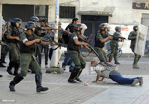 A demonstrator lies on the ground while National Guard prepare to shoot during an opposition demontration against the government of Venezuelan...