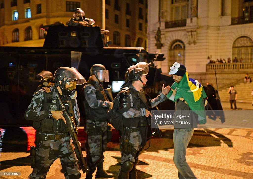 A demonstrator listens to riot police officers in Rio de Janeiro on July 11, 2013 after clashes erupted in parts of the city following a march by Brazilian workers in a day of industrial action called by major unions to press demands for better work conditions. Demonstrators on Thursday blocked roads and staged protest rallies across the country on the 'National Day of Struggles' which was called by the country's five leading labour federations during last month's mass street protests to demand better public services and an end to endemic corruption.