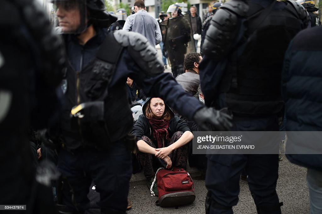A demonstrator looks on as riot police arrest protestors on May 26, 2016 in Nantes, western France, during a protest against government planned labour law reforms. The French government's labour market proposals, which are designed to make it easier for companies to hire and fire, have sparked a series of nationwide protests and strikes over the past three months. Masked youths clashed with police and striking workers blockaded refineries and nuclear power stations on May 26 as an escalating wave of industrial action against labour reforms rocked France. / AFP / JEAN