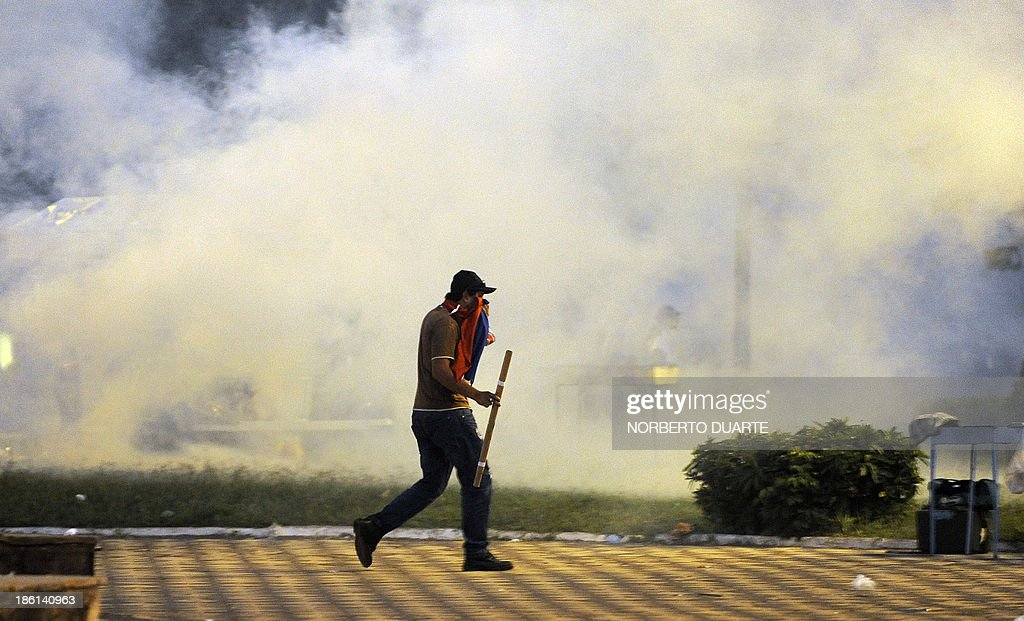 A demonstrator makes his way through tear gas after clashes with riot police in front of the National Congress, during a protest against the passing of a bill through which some public services could be privatized by only decision of the President, on October 28, 2013, in Asuncion.