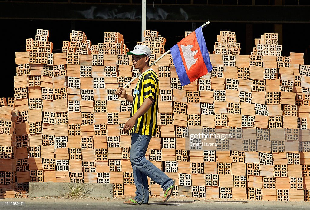 A demonstrator marches on National Road 1 holding a Cambodian flag on December 8, 2013 in Phnom Penh, Cambodia. Over 500 Cambodian monks are marching in protest from December 1 - December 10 as they head to Phnom Penh to take part in coordinated anti-government protests, which will mark the 65th International Human Rights Day. Joining them are communities, associations, networks, federations, unions and NGOs, as well as residents of communities all along the six designated routes.