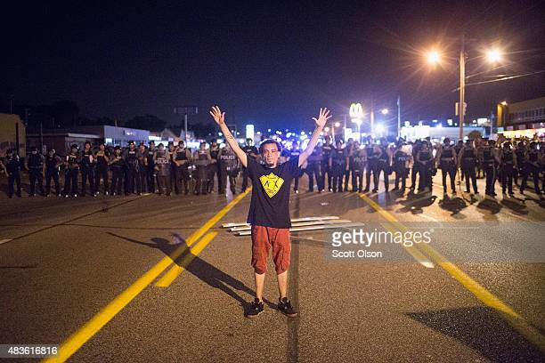 A demonstrator marking the oneyear anniversary of the shooting of Michael Brown confronts police during a protest along West Florrisant Street on...