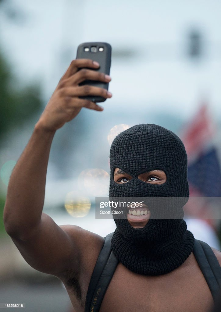 A demonstrator, marking the one-year anniversary of the shooting of Michael Brown, stops to take a selfie while protesting along West Florrisant Street on August 9, 2015 in Ferguson, Missouri. There are reports that two people were shot when gun fire broke out during protests later in the evening. Brown was shot and killed by a Ferguson police officer on August 9, 2014. His death sparked months of sometimes violent protests in Ferguson and drew nationwide focus on police treatment of black suspects.