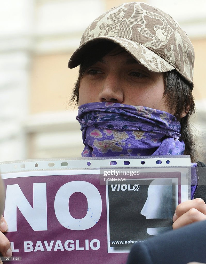 A demonstrator of the people in purple (Popolo Viola) holds a sign reading 'no to the muzzling law' during a protest in central Rome on May 21, 2010 against the government's policy on phone tapping.