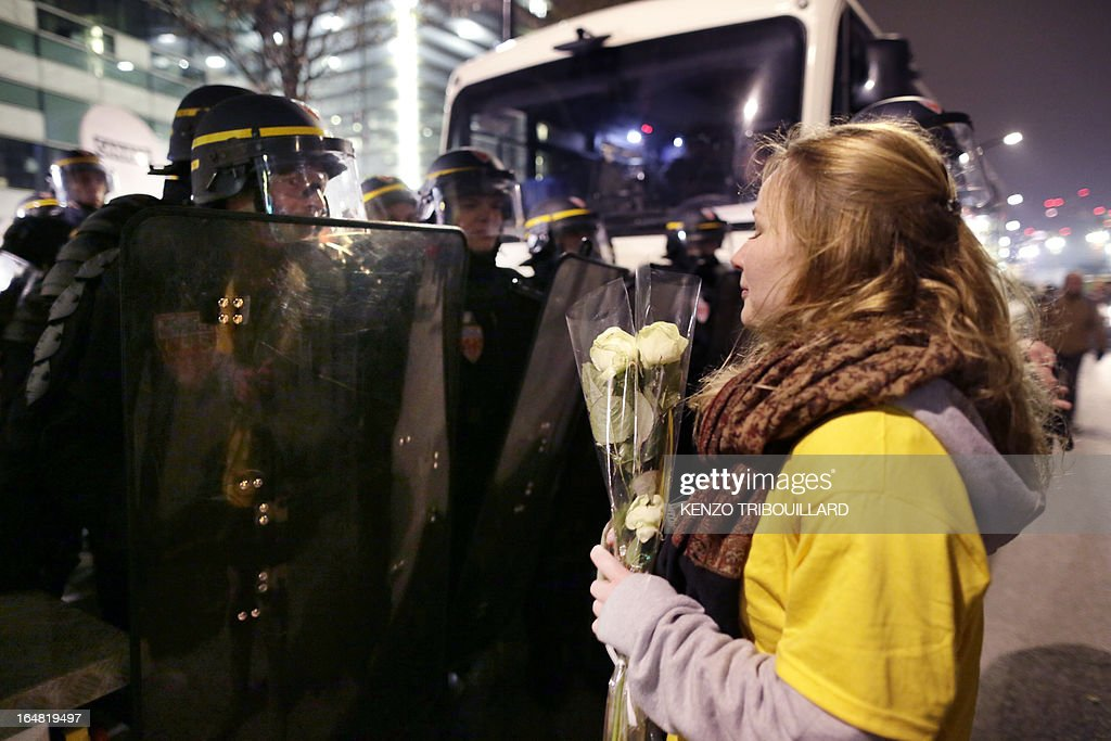 A Demonstrator opposed to same-sex marriage holds a bunch of flowers as she faces anti riot policemen during a protest on March 28, 2013 outside the headquarters of France Television group in Paris, while the French president is interviewed during the broadcast news on the TV channel France 2.