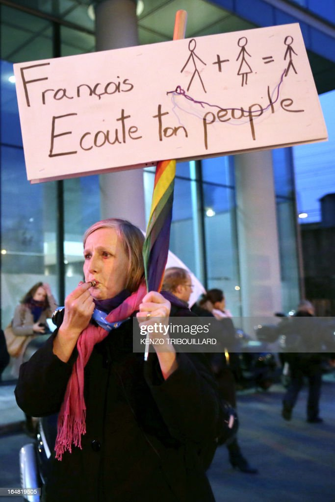 A demonstrator opposed to same-sex marriage holds a placard reading 'Francois, listen to your people' during a protest on March 28, 2013 outside the headquarters of France Television group in Paris, while the French president Francois Hollande is interviewed during the broadcast news on the TV channel France 2.