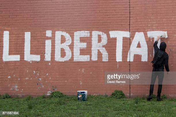 A demonstrator paints the word 'llibertat' freedom in Catalan as protestors block a ring road during a regional strike on November 8 2017 in...