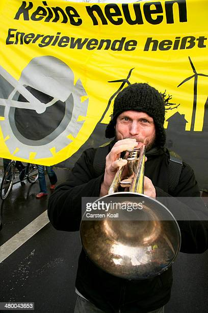 A demonstrator plays a trumpet while demonstrators march to demand a faster transition to renewable energy sources on March 22 2014 in Postdam...