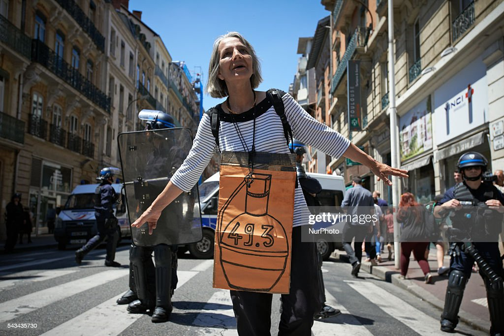 A demonstrator plays in front of riot police with a placard depicting a hand grenade with '49.3' during a protest against the El-Khomri bill on labour reforms the day the bill go through the Senate. They also protest against the use of article 49.3 which bypass the Parliament . Toulouse. France. June 28th, 2016.