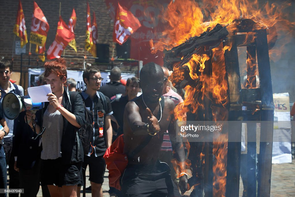 A demonstrator plays with the fire of a false coffin symbolizing democracy in front of the Prefecture of Toulouse at the end of a demonstration against the El-Khomri bill on labour reforms the day the bill go through the Senate. They also protest against the use of article 49.3 which bypass the Parliament . Toulouse. France. June 28th, 2016.