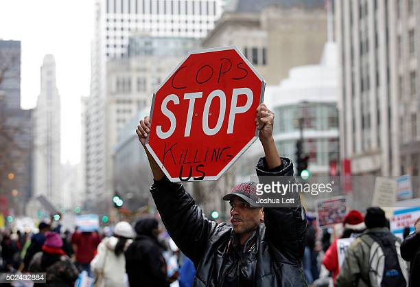 A demonstrator protesting the fatal police shooting of Laquan McDonald holds up a sign during an attempt to disrupt holiday shoppers along Michigan...