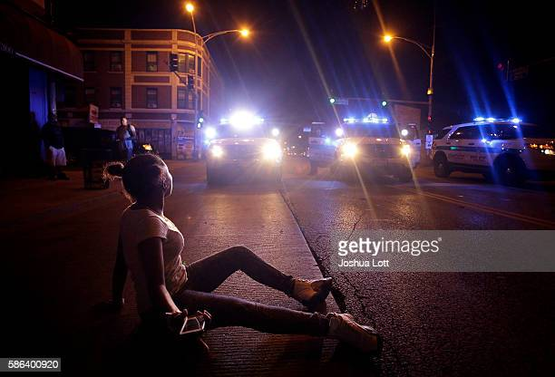 A demonstrator protesting the fatal police shooting of Paul O'Neal lays in the street in front of a police vehicle on August 5 2016 in Chicago...