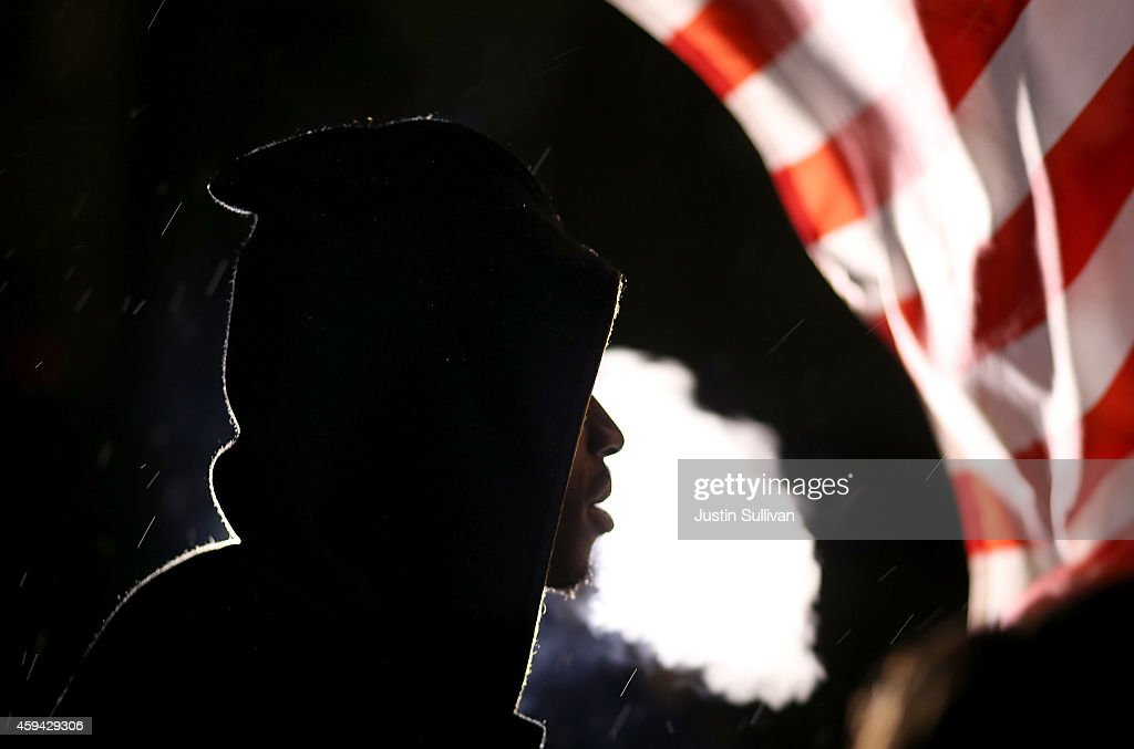 A demonstrator protesting the shooting death of 18-year-old Michael Brown blows cigar smoke on November 22, 2014 in Ferguson, Missouri. Tensions in Ferguson remain high as a grand jury is expected to decide this month if Ferguson police officer Darren Wilson should be charged in the shooting death of Michael Brown.