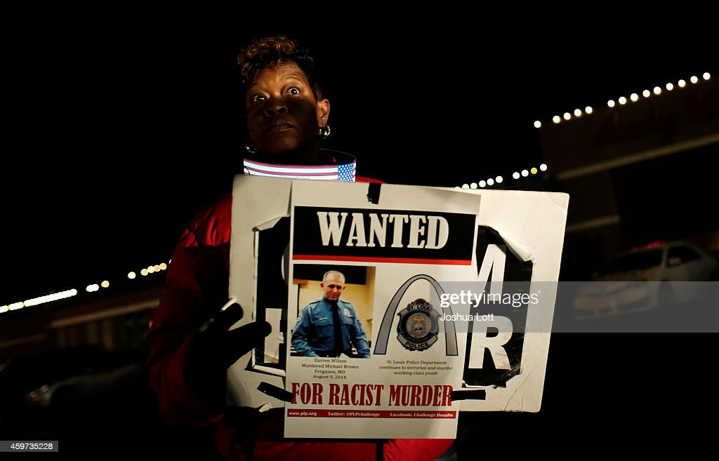 A demonstrator protesting the shooting death of Michael Brown holds a water poster of Ferguson Police officer <a gi-track='captionPersonalityLinkClicked' href=/galleries/search?phrase=Darren+Wilson+-+Police+Officer&family=editorial&specificpeople=13495859 ng-click='$event.stopPropagation()'>Darren Wilson</a> November 29, 2014 in Ferguson, Missouri. Brown, a 18-year-old black male teenager was fatally wounded by Wilson, a white Ferguson, Missouri Police officer on August 9, 2014. A St. Louis County 12-member grand jury who reviewed evidence related to the shooting decided not to indict Wilson with charges sparking riots through out Ferguson.