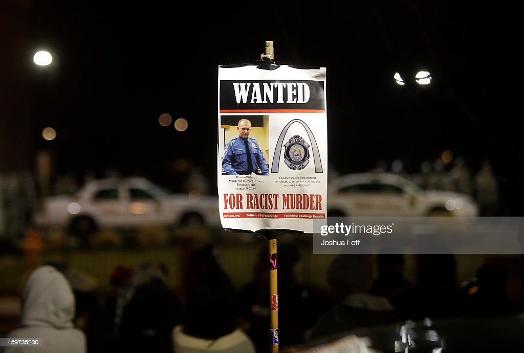 A demonstrator protesting the shooting death of Michael Brown holds a water poster of Ferguson Police officer <a gi-track='captionPersonalityLinkClicked' href=/galleries/search?phrase=Darren+Wilson+-+Police+Officer&family=editorial&specificpeople=13495859 ng-click='$event.stopPropagation()'>Darren Wilson</a> across from the Ferguson Police Station November 29, 2014 in Ferguson, Missouri. Brown, a 18-year-old black male teenager was fatally wounded by Wilson, a white Ferguson, Missouri Police officer on August 9, 2014. A St. Louis County 12-member grand jury who reviewed evidence related to the shooting decided not to indict Wilson with charges sparking riots through out Ferguson.