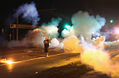 A demonstrator protesting the shooting death of teenager Michael Brown stands his ground as police fire tear gas on August 13 2014 in Ferguson...