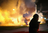 A demonstrator protesting the shooting death of teenager Michael Brown scrambles for cover as police fire tear gas on August 13 2014 in Ferguson...