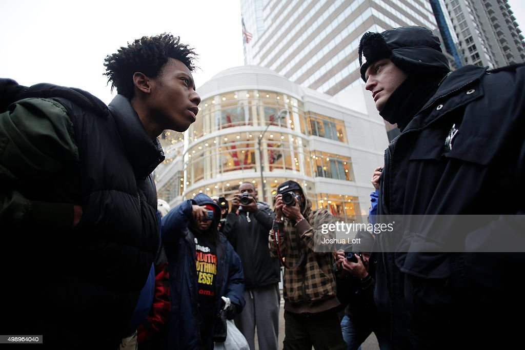 A demonstrator protesting the shooting of Laquan McDonald who was killed by a Chicago police Officer stares down a police Officer along the Michigan Avenue also known as the Magnificent Mile November 27, 2015 in Chicago, Illinois. Chicago police Officer Jason Van Dyke was charged Tuesday with first degree murder for fatally shooting 17-year-old McDonald 16 times last year on the southwest side of Chicago after Van Dyke was responding to a call of a knife wielding man. The dash-cam video of Officer Van Dyke shooting McDonald was released by the Chicago Police department earlier this week after a judge denied Van Dyke bail during his bond hearing at Leighton Criminal Court.