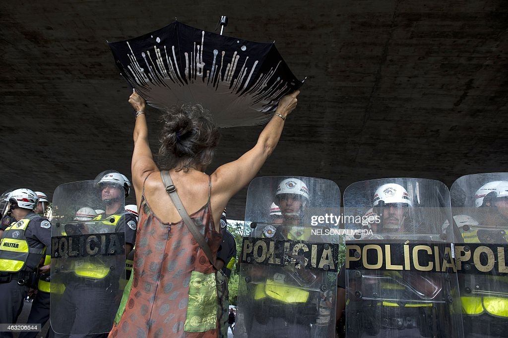 A demonstrator protests over the lack of water in front of a riot police barricade at Paulista Avenue in Sao Paulo Brazil on February 11 2015 The...