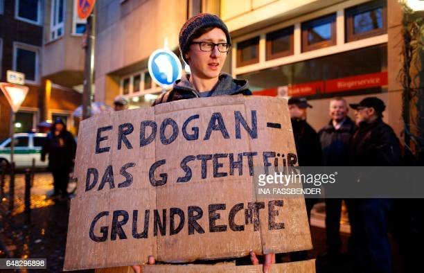 A demonstrator protests with a placard which read 'Erdogan the G stands for fundamental rights' at the Senators Hotel in Cologne western Germany on...