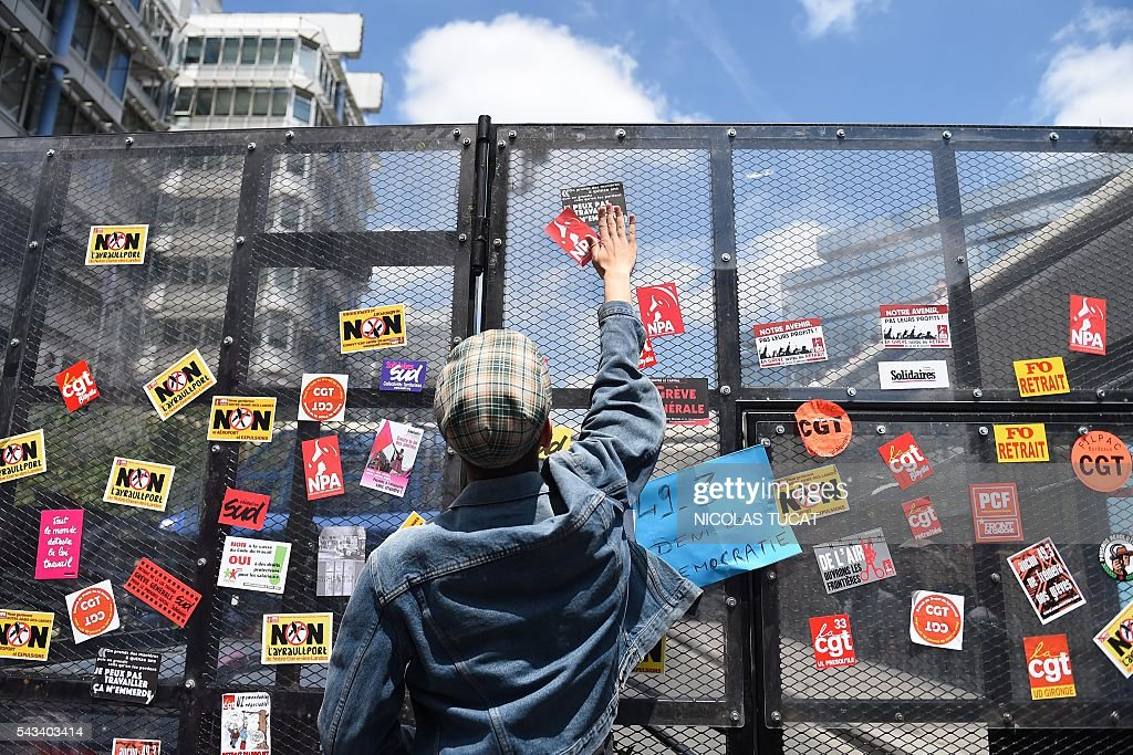 A demonstrator put stickers on an anti riot wall during a demonstration against proposed labour law reforms in Bordeaux on June 28, 2016.v Unions have called repeated strikes and marches against controversial labour reforms, forced through by the government of Socialist President Francois Hollande. / AFP / NICOLAS