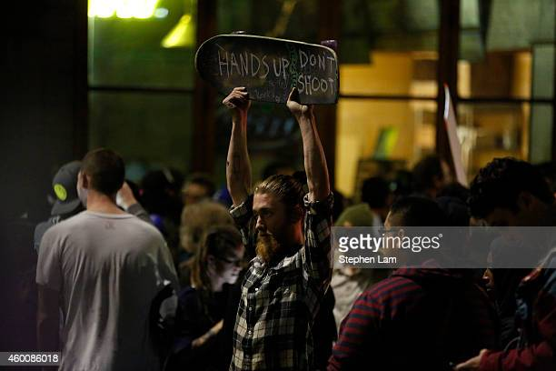 A demonstrator raises a sign on his skateboard after being surrounded by the police on the fourth night of demonstrations over recent grand jury...