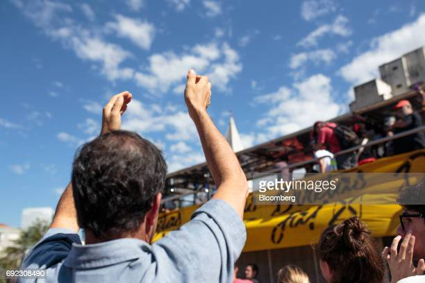 A demonstrator raises his hands as musicians play on a platform during a protest against Brazilian President Michel Temer and government corruption...