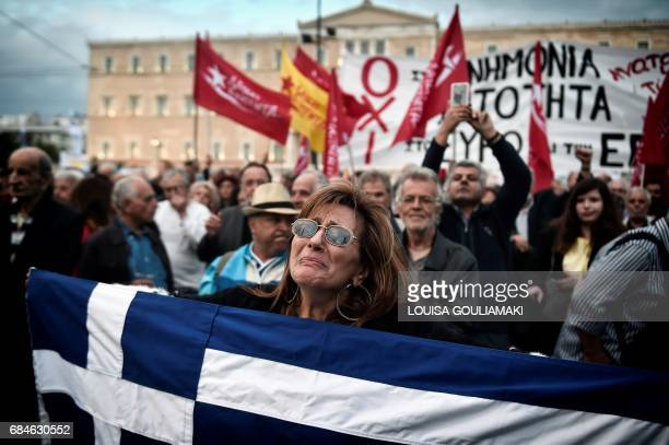 TOPSHOT A demonstrator reacts while holding the Greek national flag outside the Greek parliament on May 18 during a demonstration on the sidelines of...