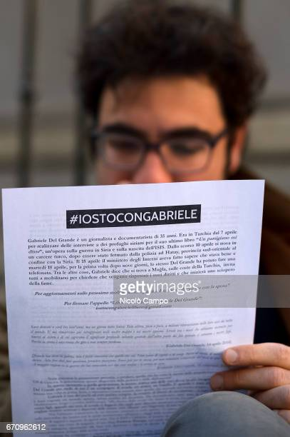 A demonstrator reads a flyer during a rally to demand the release of the Italian journalist blogger writer and human rights activist Gabriele Del...