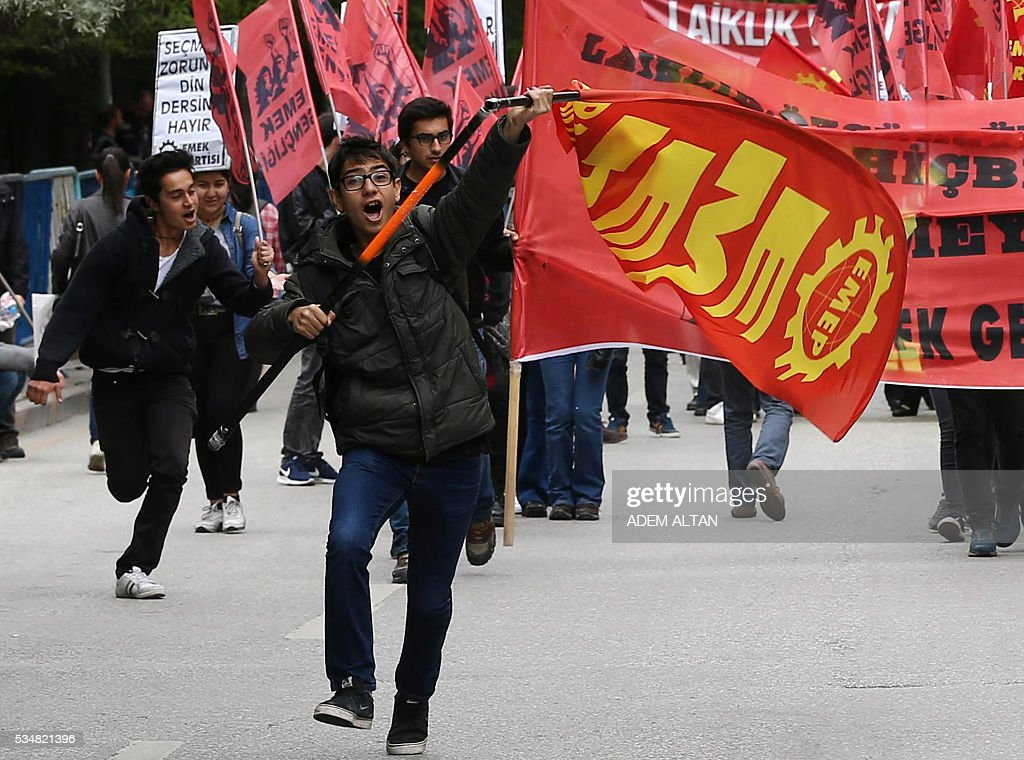 Demonstrator run and wave banners during an anti-government, pro-secularism protest by Turkish worker unions on May 28, 2016 in Ankara. Turkish President Recep Tayyip Erdogan on May 22 gave his close ally and Transport Minister Binali Yildirim the mandate to form a government as prime minister in a move set to further consolidate the strongman's grip on power. Yildirim is only the third party chairman in the history of the AKP -- which has transformed Turkey by putting Islam at the forefront of the officially secular country's politics -- after Erdogan and Davutoglu. / AFP / ADEM