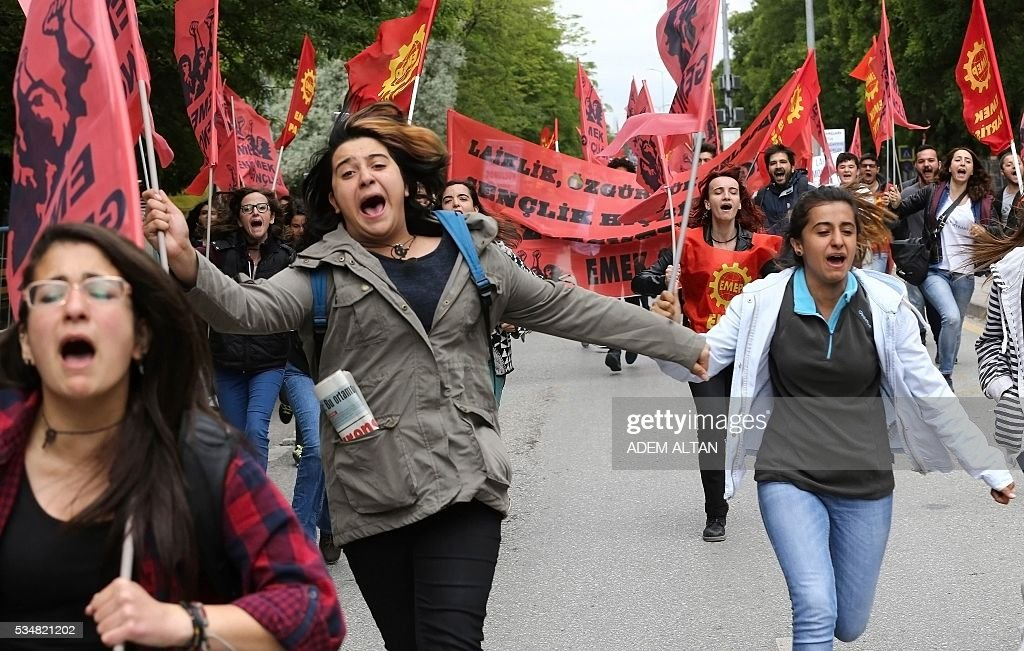 Demonstrator run during an anti-government, pro-secularism protest by Turkish worker unions on May 28, 2016 in Ankara. Turkish President Recep Tayyip Erdogan on May 22 gave his close ally and Transport Minister Binali Yildirim the mandate to form a government as prime minister in a move set to further consolidate the strongman's grip on power. Yildirim is only the third party chairman in the history of the AKP -- which has transformed Turkey by putting Islam at the forefront of the officially secular country's politics -- after Erdogan and Davutoglu. / AFP / ADEM