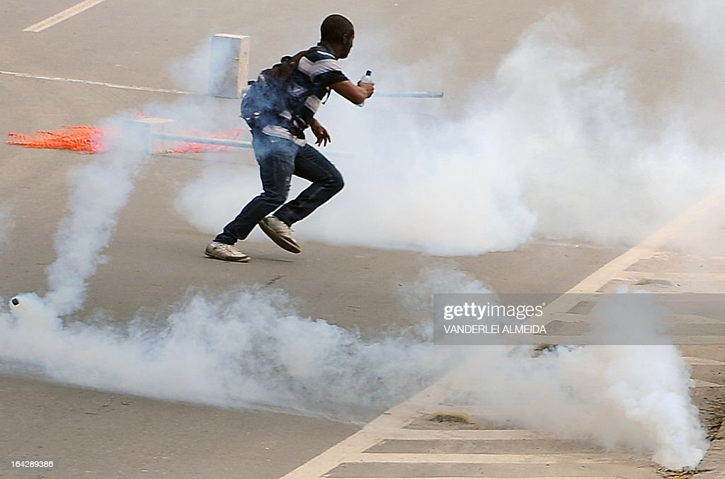 A demonstrator runs between tear gas launched by riot police forces during a protest against the eviction of native people from the former Indigenous Museum --aka Aldea Maracana-- next to the Maracana stadium in Rio de Janeiro, Brazil on March 22, 2013. Indigenous people have been occupying the place since 2006, which is due to be pulled down to construct a parking lot for the upcoming Brazil 2014 FIFA World Cup.