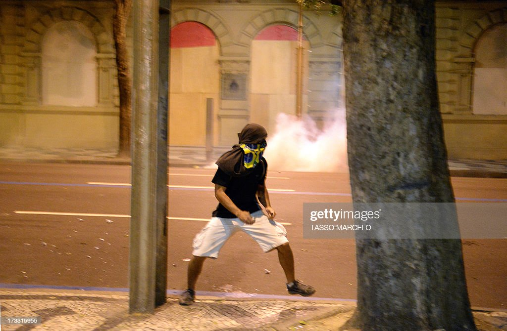 A demonstrator runs during clashes with the riot police which erupted after a march by Brazilian workers in Rio de Janeiro on July 11, 2013 in a day of industrial action called by major unions to press demands for better work conditions. Demonstrators on Thursday blocked roads and staged protest rallies across the country on the 'National Day of Struggles' which was called by the country's five leading labour federations during last month's mass street protests to demand better public services and an end to endemic corruption. AFP PHOTO / TASSO MARCELO