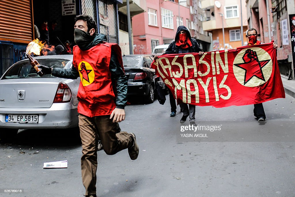 A demonstrator (L) runs with a molotov cocktail during a May Day rally in the Okmeydani neighbourhood of Istanbul on May 1, 2016. Turkish police clamped down on unauthorised protests during a tense May Day in Istanbul, using tear gas and water cannon against demonstrators and imposing a heavy security blanket on the city. / AFP / YASIN