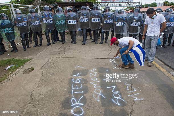 A demonstrator scribbles on the tarmac an inscription that reads 'Ortega and Somoza same shit' in front of a line of riot police during a protest...