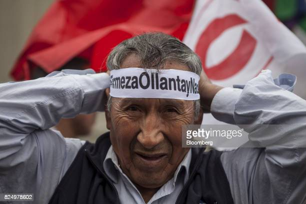 A demonstrator secures a bandanna during a protest against the detention of former Peruvian President Ollanta Humala and his wife Nadine Heredia...
