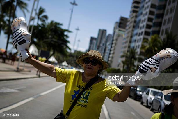 A demonstrator shakes up dolls of former President Lula dressed as a prisoner Members of the popular Somos Mais Brasil movement protest against...