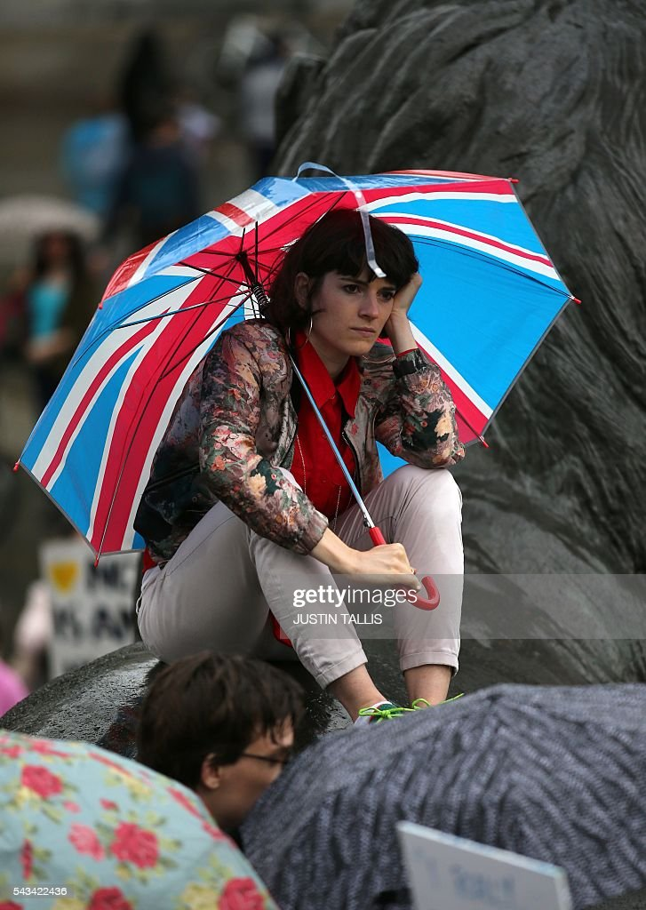 A demonstrator shelters under a Union flag umbrella people gather for an anti-Brexit protest in Trafalgar Square in central London on June 28, 2016. EU leaders attempted to rescue the European project and Prime Minister David Cameron sought to calm fears over Britain's vote to leave the bloc as ratings agencies downgraded the country. Britain has been pitched into uncertainty by the June 23 referendum result, with Cameron announcing his resignation, the economy facing a string of shocks and Scotland making a fresh threat to break away. / AFP / JUSTIN