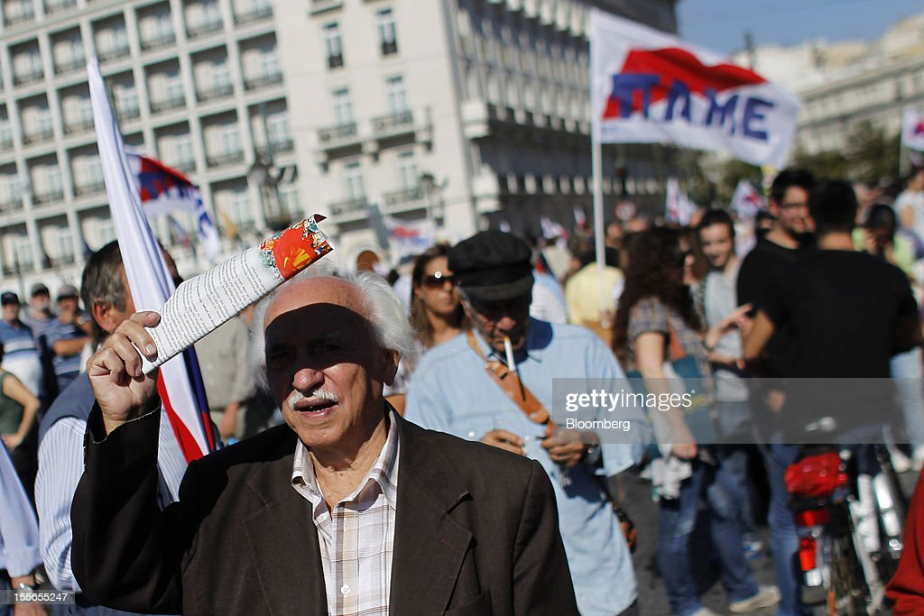 A demonstrator shields his eyes from the sun during a general strike protest in Athens, Greece, on Tuesday, Nov. 6, 2012. Greece headed for a cliffhanger vote on austerity measures needed to keep the bailout on track as a 48-hour general strike began and European officials squabbled over the timing of a deal to unlock rescue funds. Photographer: Kostas Tsironis/Bloomberg via Getty Images