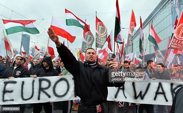 A demonstrator shouts and performs a Nazi salute in front of banner reading 'Europe awake' followed by a group of Hungarian Jobbik party...