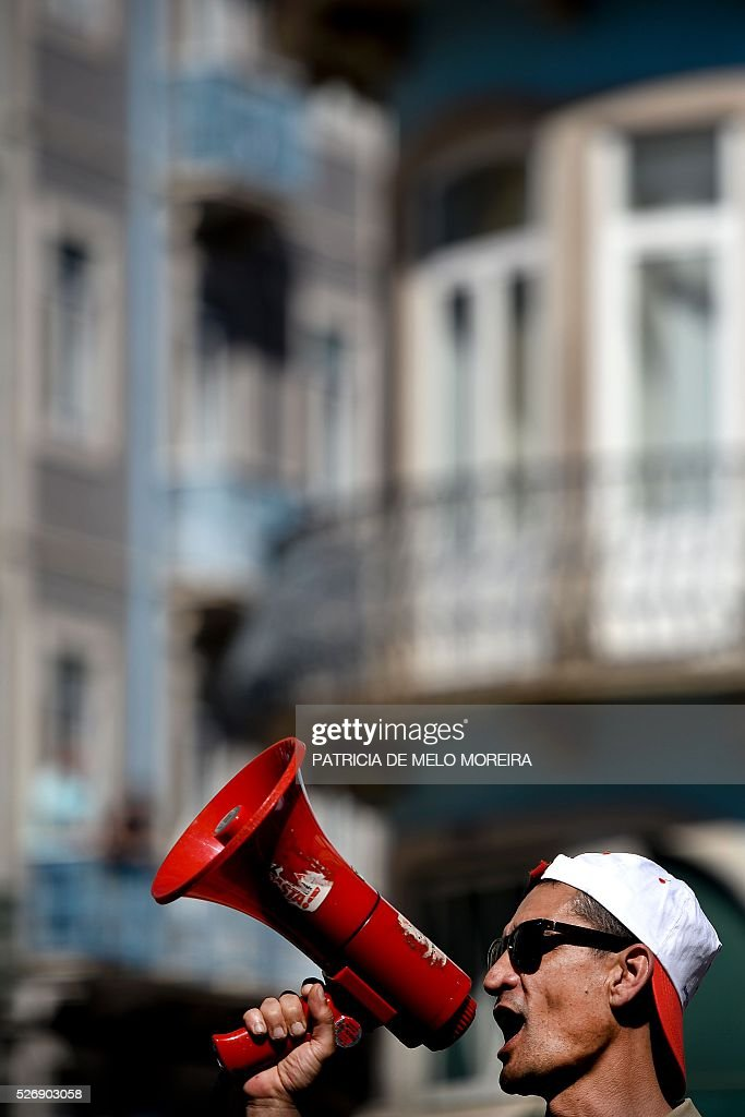 A demonstrator shouts slogans during the traditional May Day rally in Lisbon on May 1, 2016. Thousands of people demonstrated today in Lisbon and Portugal's main cities against the government's austerity measures. / AFP / PATRICIA