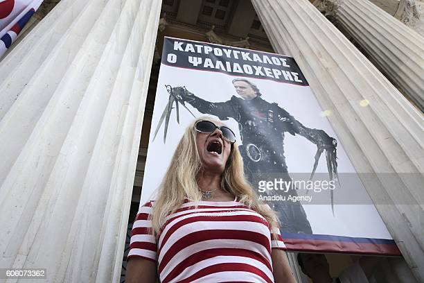 A demonstrator shouts slogans in front of the poster of Labor Minister George Katrugalos who is portrayed as a famous movie character Edward...