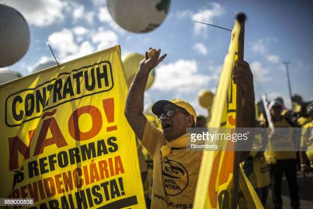 A demonstrator shouts while holding a flag during protests outside of the National Congress demanding the resignation of President Michel Temer in...