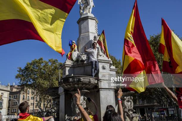 A demonstrator shouts while standing on a fountain during a protest for Spanish unity at the Pla de Palau square in Barcelona Spain on Sunday Oct 8...