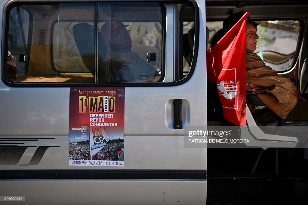 A demonstrator sits in a van with a poster reading '1st May, defend, replace, conquer' during the traditional May Day rally in Lisbon on May 1, 2016. Thousands of people demonstrated today in Lisbon and Portugal's main cities against the government's austerity measures. / AFP / PATRICIA