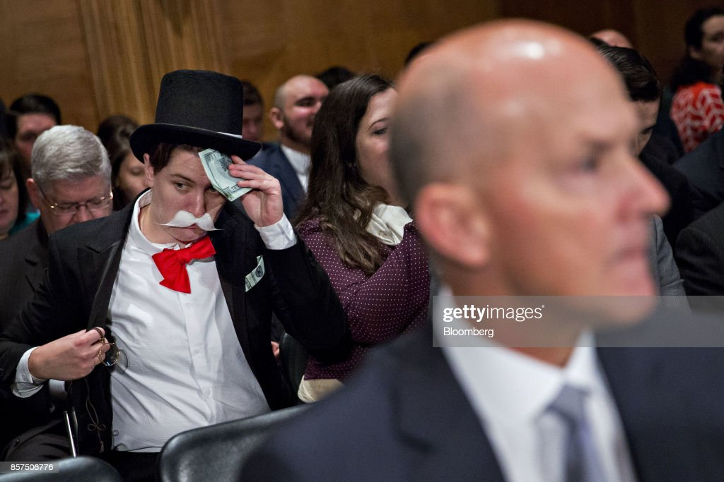 A demonstrator sits in costume behind Richard Smith, former chairman and chief executive officer of Equifax Inc., right, before a Senate Banking Committee hearing in Washington, D.C., U.S., on Wednesday, Oct. 4, 2017. Lawmakers grilled Smith on Tuesday after hackers attacked the company's systems and got access to sensitive information for 145.5 million Americans. Photographer: Andrew Harrer/Bloomberg via Getty Images