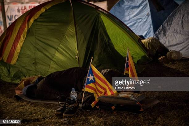 A demonstrator sleeps next to Catalan ProIndependence flags 'Estelada' in front of the Catalan High Court building on September 22 2017 in Barcelona...